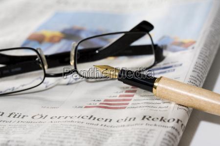 stift und brille auf zeitung nahaufnahme