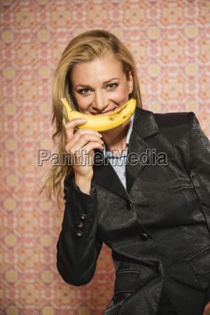 germany stuttgart businesswoman with banana smiling