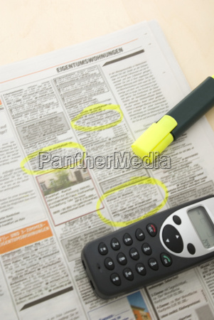 mobile phone and pen on newspaper