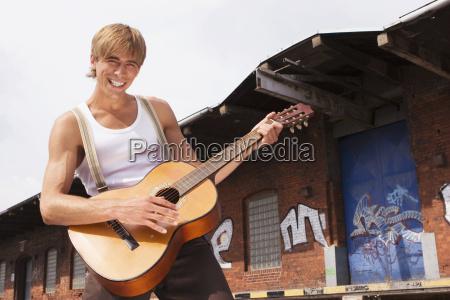 man playing guitar smiling portrait