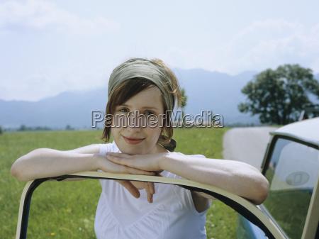 frau lehnt am auto