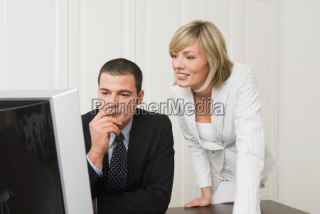 business people looking at computer in
