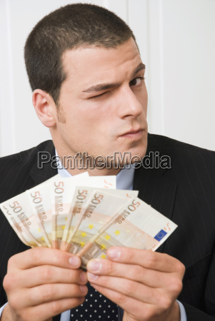 young man holding euro banknotes portrait