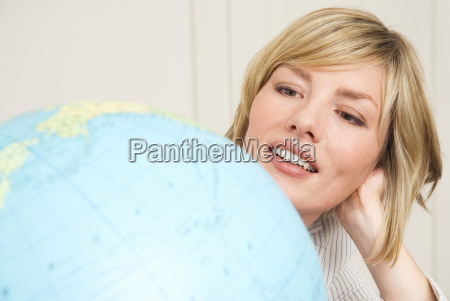 young businesswoman looking at globe portrait