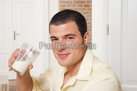 smiling young man holding a glass