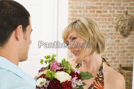 man giving bunch of flowers to