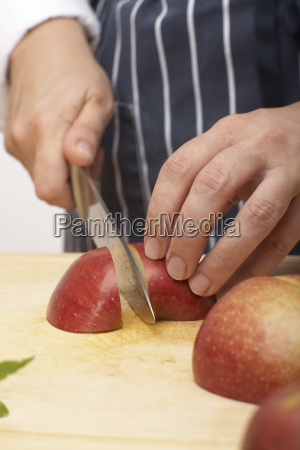 person cutting an apple into quarters