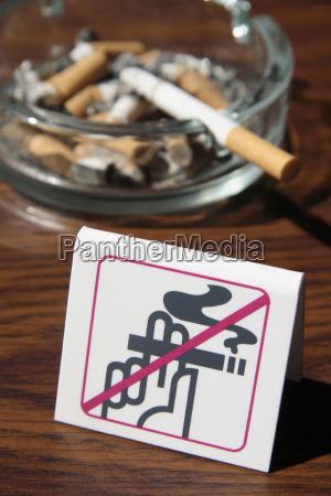 voller aschenbecher hinter rauchverbot nahaufnahme