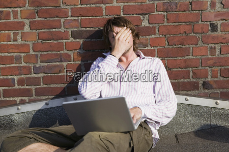 man using laptop leaning by wall