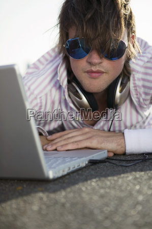young man lying by laptop wearing