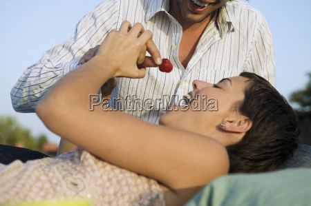 young man feeding woman strawberry close