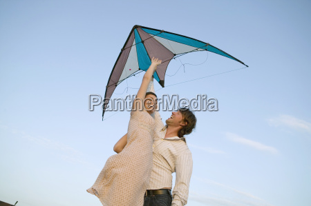 young couple flying kite low angle