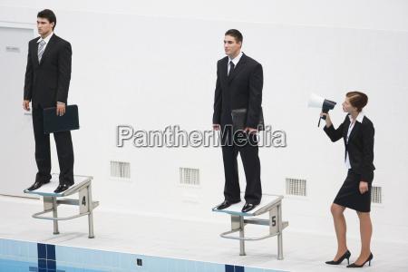 businessmen standing on staring blocks woman