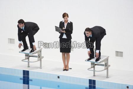 businessmen on starting blocks woman writing