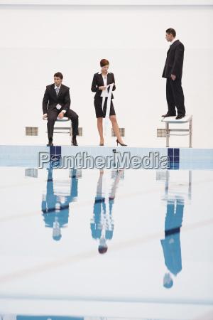 businessmen on starting blocks woman holding