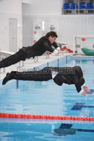 businessmen jumping in pool