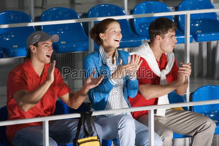 young people sitting on tribune clapping