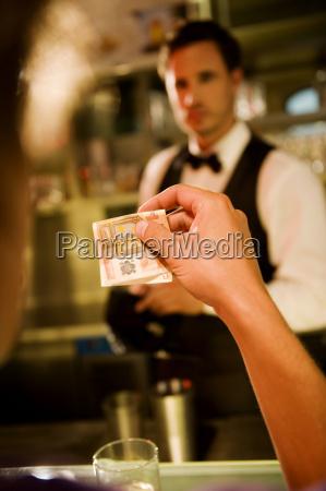 mann ueberreicht geld an barkeeper