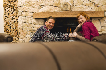 couple sitting by fireside smiling