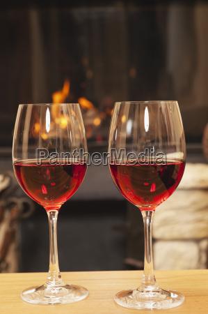 zwei glaeser rotwein vor dem kamin