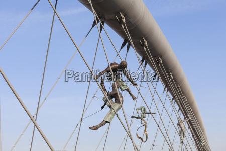 haengende eisenfiguren balancieren auf seilen auf