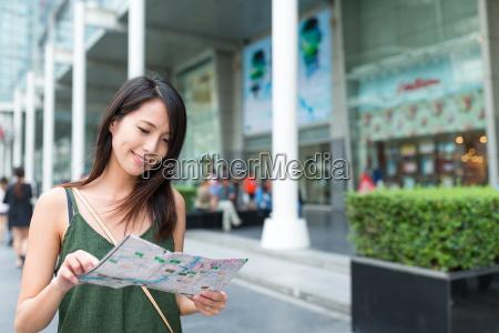 woman using city map in bangkok