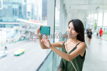 woman taking photo with cellphone in
