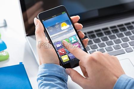 frau nutzt smart phone mit anwendungen