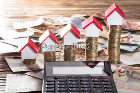 miniature houses resting on increasing coin