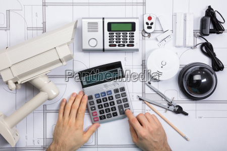 male engineer using calculator with security
