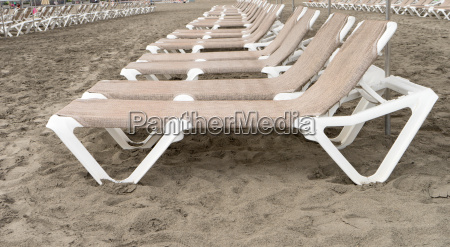 row with empty beach chairs at