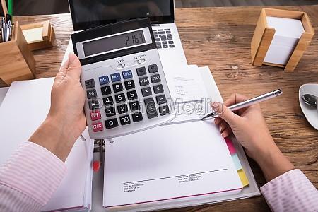 businesswoman calculating invoice on desk