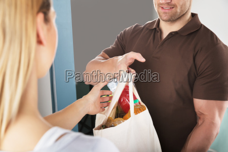 man giving bag of grocery to