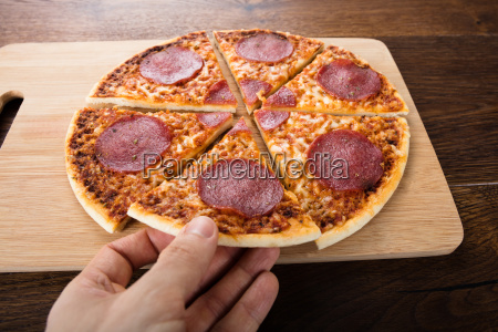 hand holding slice of salami pizza