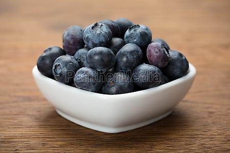 heap of fresh blueberries in white
