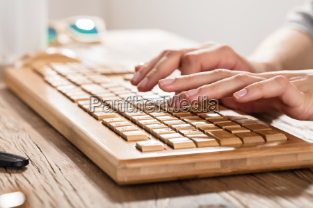 womans hand on wooden keyboard