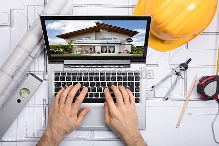 an architect using laptop on blueprint