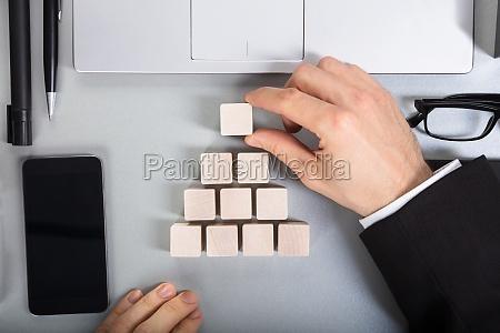 businessperson arranging wooden block on desk
