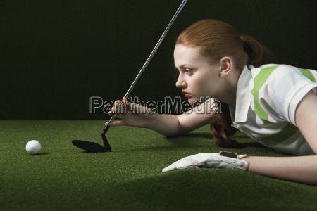 woman on floor holding golf club