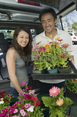 couple loading flowers into back of