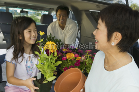 family loading flowers into back of