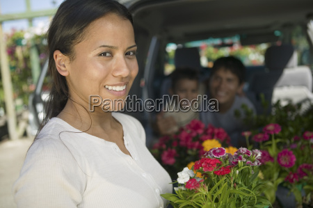 mother standing by back of minivan