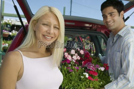 couple loading plants into minivan portrait