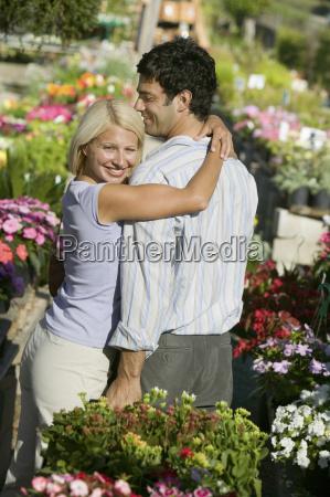 couple at plant nursery hugging