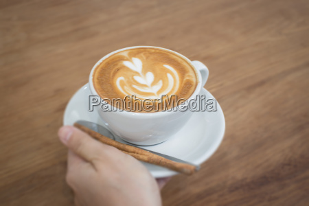 hand on hot cup of coffee