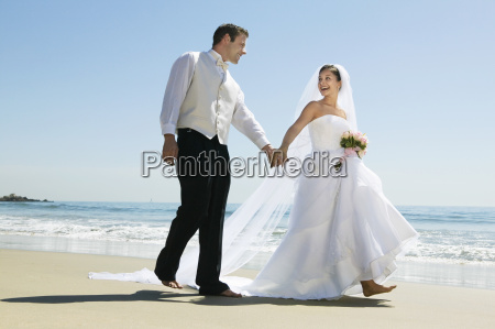 newlywed couple holding hands while walking