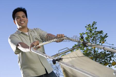 mid adult man holding land mower