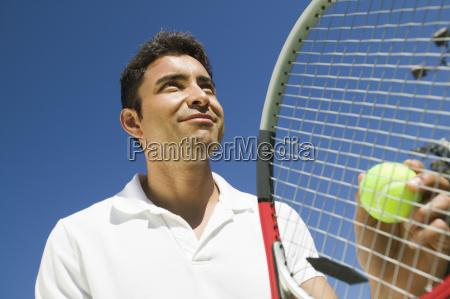 male tennis player preparing to serve