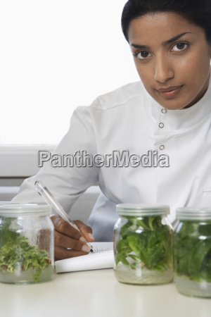 scientist examining plant material while recording