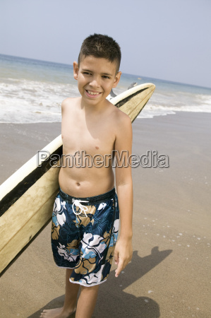 portrait of boy holding surfboard on